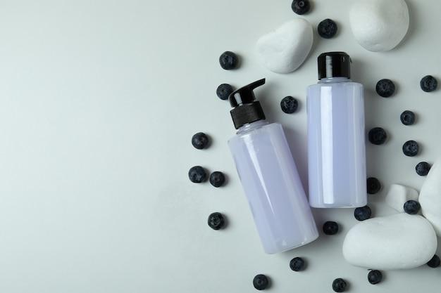 Duschgels, blaubeeren und steine auf weißem hintergrund