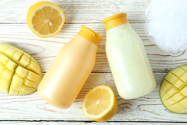 Duschgels, mango und zitrone auf weißem holz