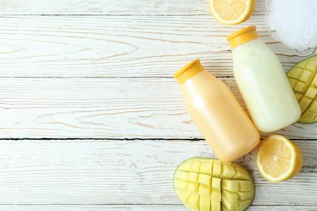 Duschgels, mango und zitrone auf weißem holzhintergrund
