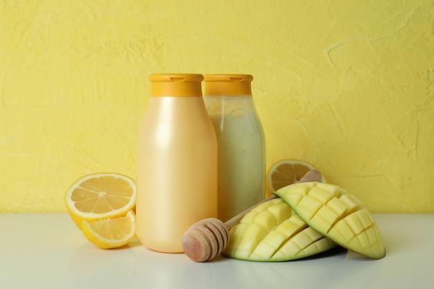 Duschgels, mango und zitrone vor gelbem hintergrund