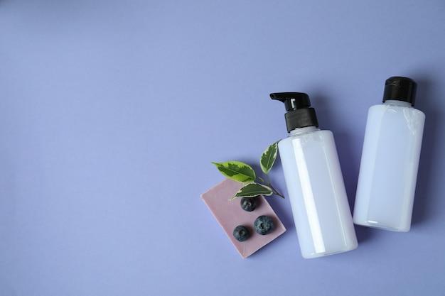 Duschgels, seife und blaubeere auf violettem hintergrund