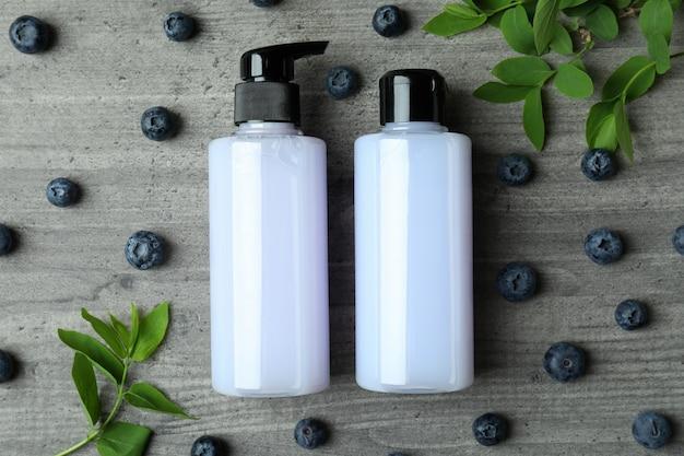 Duschgels und blaubeeren auf grauem strukturiertem hintergrund