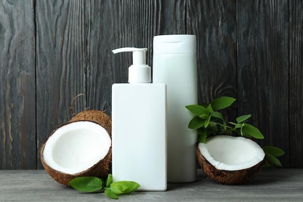 Duschgels und kokosnuss gegen hölzernen hintergrund