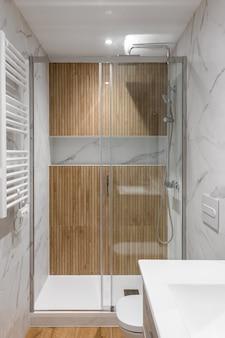 Duschzone mit holzveredelung und glastür im inneren des modernen renovierten badezimmers