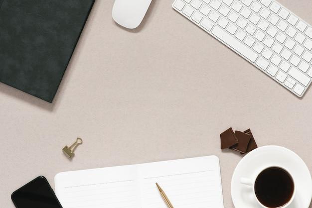 Dusty coffee office schreibtisch mit computer, tagebuch mit stift, tasse kaffee mit schokoladenstücken, telefon. draufsicht mit kopierraum, flach gelegt.