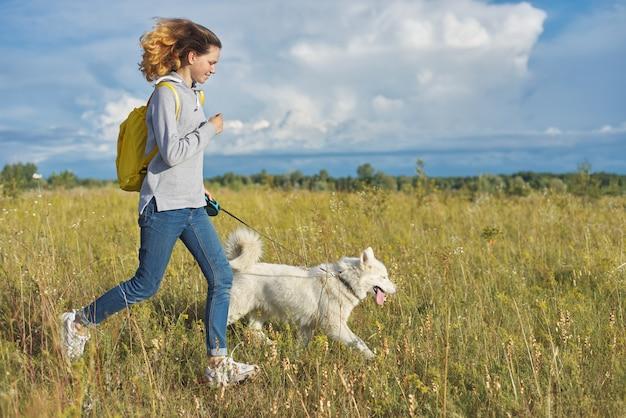 Dynamisches außenporträt des laufenden mädchens mit hund