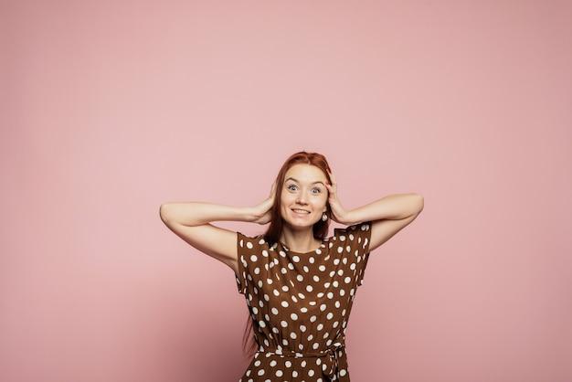 Dynamisches bild des kaukasischen weiblichen modells auf rosa wand. erfolgreiche glückliche frau, die feiert, ein gewinner zu sein. sieg, freude konzept. konzept der menschlichen gesichtsgefühle. trendige farben