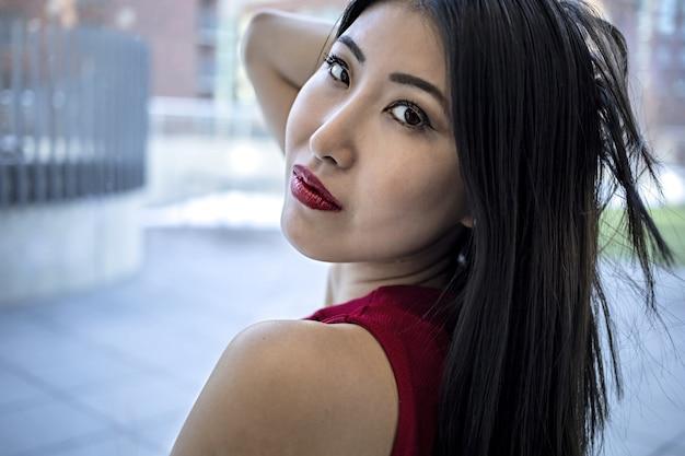 E asiatisches model, das ein modisches elegantes rotes kleid und einen glänzenden roten lippenstift trägt