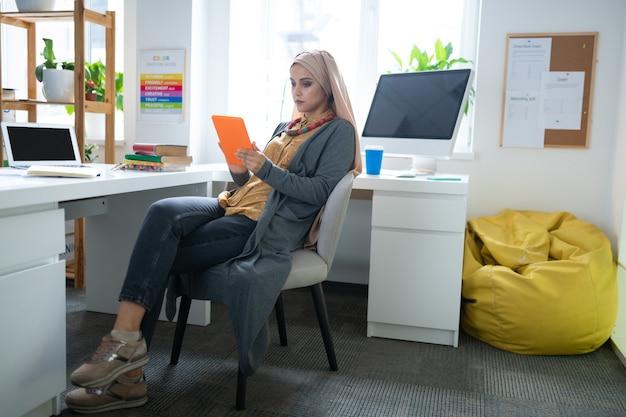 E-book lesen. moderne muslimische lehrerin, die ihr orangefarbenes tablet benutzt, während sie ein e-book liest