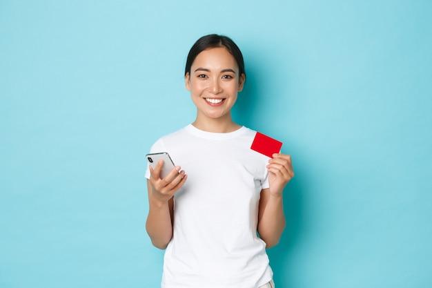E-commerce-, einkaufs- und lifestyle-konzept. schönes lächelndes asiatisches mädchen, das kleidung online kauft, mit smartphone und kreditkarte, für bestellung zahlend, blaue wand.