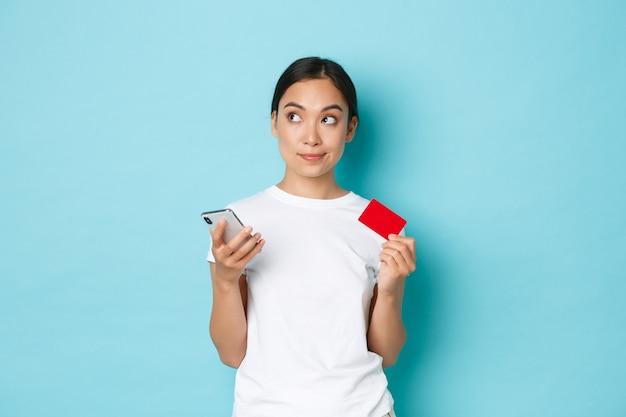 E-commerce-, einkaufs- und lifestyle-konzept. unentschlossenes nachdenkliches asiatisches mädchen im weißen t-shirt, weg denkend, während kreditkarte und smartphone halten, online-bestellung machen.