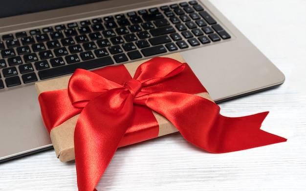 E-commerce-gadgets speichern website-rabatte und geschenk, tisch mit laptop und geschenkbox auf tisch