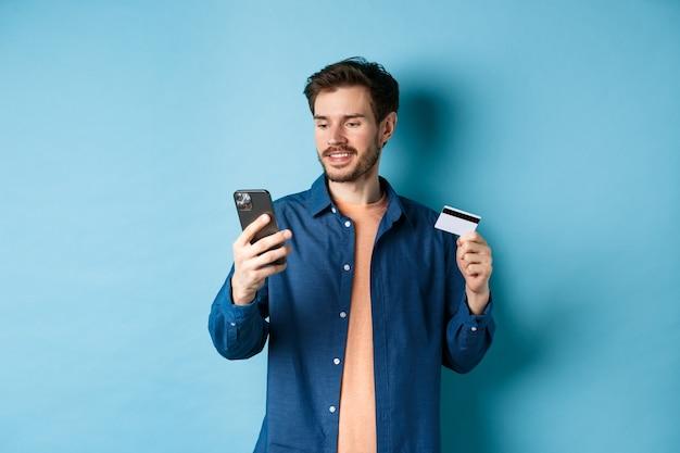 E-commerce-konzept. bild des hübschen kaukasischen mannes, der online zahlt, den handybildschirm betrachtet und plastikkreditkarte, blauen hintergrund hält.