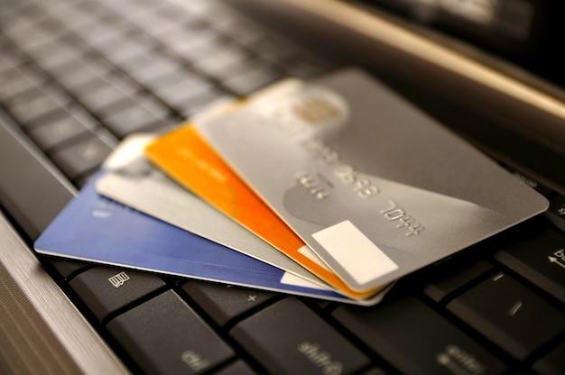 E-commerce-konzept. gruppe von kreditkarten und laptop mit flachem dof