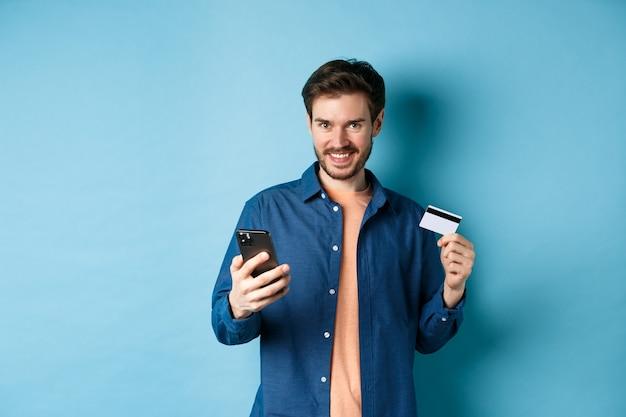 E-commerce-konzept. hübscher junger mann, der online einkauft, smartphone und plastikkreditkarte hält, kamera lächelnd, auf blauem hintergrund stehend.
