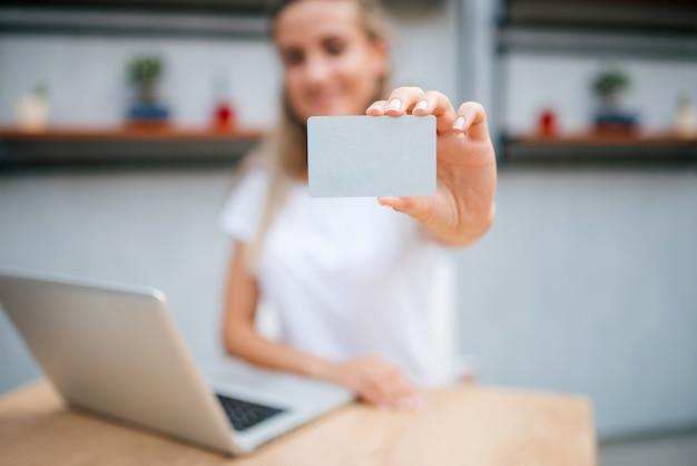 E-commerce-konzept. junge frau, die eine kreditkarte anhält. der schwerpunkt liegt auf der karte.