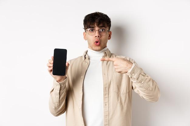 E-commerce-konzept. porträt eines jungen mannes, der auf den bildschirm eines mobiltelefons zeigt, werbung online zeigt und auf weißem hintergrund steht