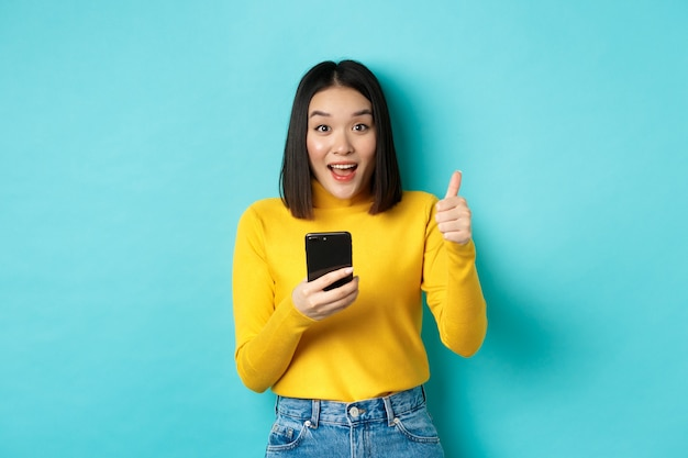 E-commerce- und online-shopping-konzept. aufgeregte und erstaunte asiatische frau, die nach der verwendung der smartphone-app daumen nach oben zeigt, gerät empfehlen, auf blauem hintergrund stehend.