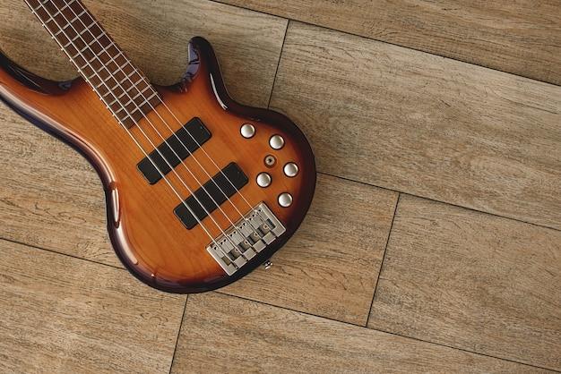 E-gitarren-sounds. draufsicht auf den körper der e-gitarre gegen den holzboden. musikanlage. musikinstrumente. musikkonzept