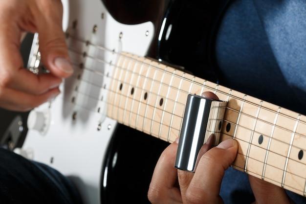 E-gitarrist, der lied mit schieberegler durchführt