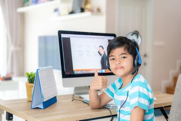 E-learning der asiatischen studentenjungen-videokonferenz mit lehrer am computer und daumen hoch