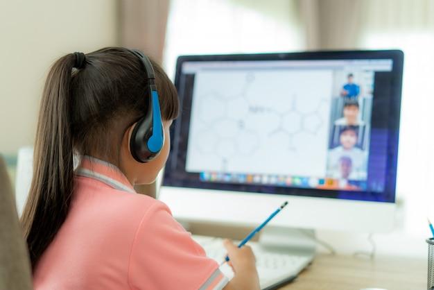 E-learning der asiatischen studentin der videokonferenz mit lehrer und klassenkameraden am computer im wohnzimmer zu hause. homeschooling und fernunterricht, online, bildung und internet.