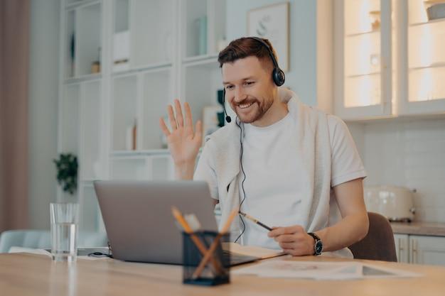 E-learning-konzept. glücklicher bärtiger mann student hat videokonferenzstudien online wellen palm im laptop-display grüßt lehrer arbeitet entfernt verwendet headset macht notizen in tagebuch-posen über die inneneinrichtung
