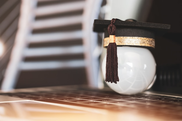 E-learning-onlineabsolvent-bildungskonzept, glückwunschabsolvent auf laptop-computerunschärfegebäude