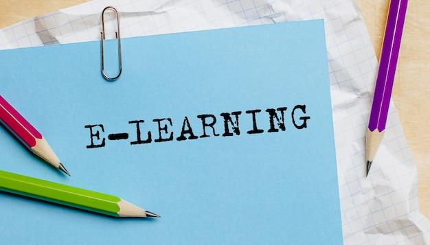 E-learning-text auf einem papier mit stiften im büro geschrieben