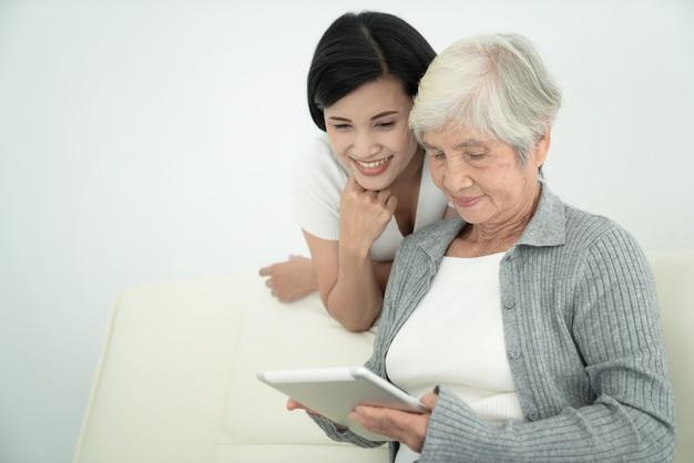 Ealry mutter mit tochter mit digitalem tablet zusammen zu hause. lächelnde familie, die bildschirm betrachtet, online einkauft