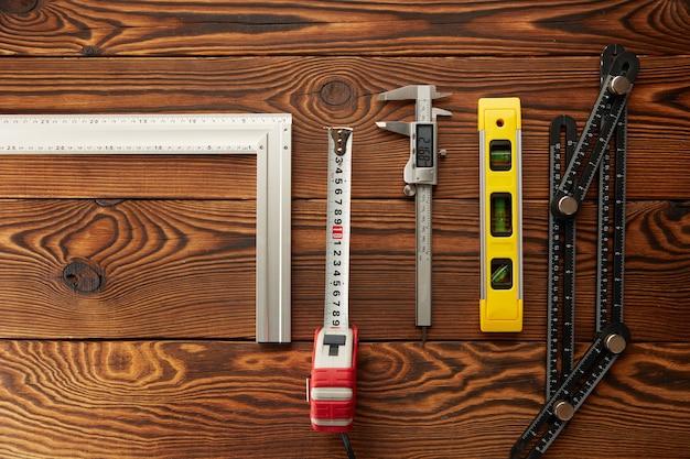 Ebene und ecke, lineal und bremssattel, draufsicht. professionelles messgerät, tischlerausrüstung, holzwerkzeuge