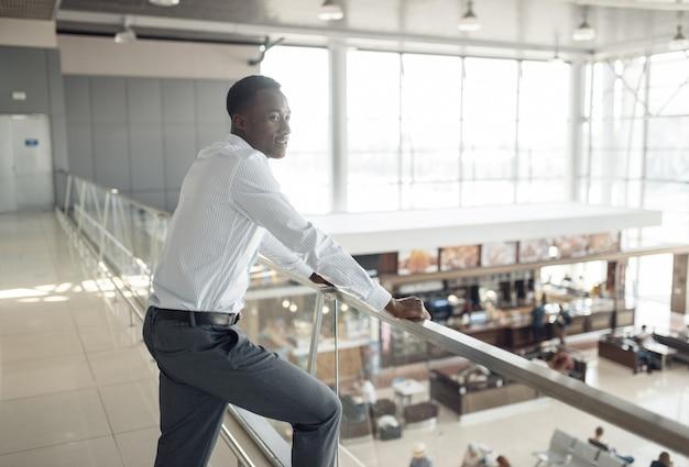 Ebenholzgeschäftsmann, der auf food-court im einkaufszentrum schaut. erfolgreicher geschäftsmann, schwarzer mann in formeller kleidung, einkaufszentrum