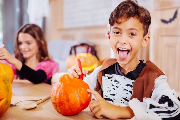 Echte aufregung. netter strahlender junge, der halloween-kostüm trägt, das seine zunge zeigt, während er sich aufgeregt fühlt