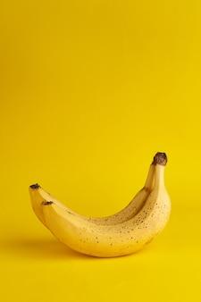 Echte bananen mit braunen punkten und lücken auf gelbem hintergrund. vertikales banner. platz für text