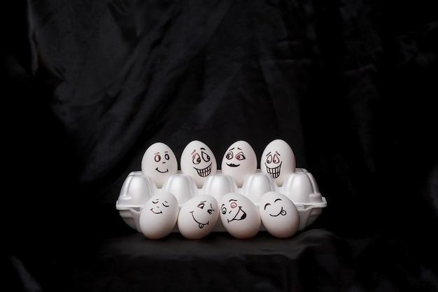 Echte handbemalte eier. weiße eier mit den gezeichneten gesichtern vereinbart im karton.