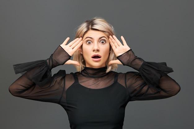 Echte menschliche emotionen und gefühle. emotionales schönes blondes mädchen in trendigen kleidern und accessoires, die echte unerwartete reaktion auf unerwartete nachrichten ausdrücken und ungläubig den mund öffnen
