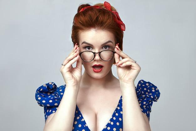 Echte menschliche emotionen und reaktionen. modisches pin-up-girl, das ein blaues retro-kleid und einen roten lippenstift trägt und sie erstaunt anstarrt