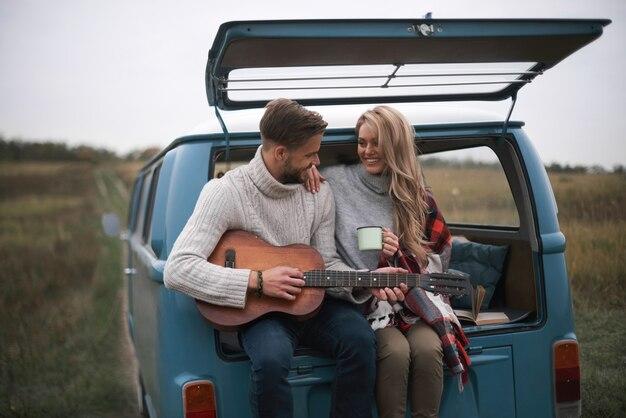 Echte seelenverwandte. hübscher junger mann, der gitarre für seine schöne freundin spielt, während er im kofferraum des blauen minivans im retro-stil sitzt