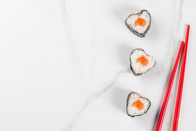 Echte sushi zum valentinstag in form von herzen gesetzt. draufsicht des weißen marmorhintergrundkopien-raumes