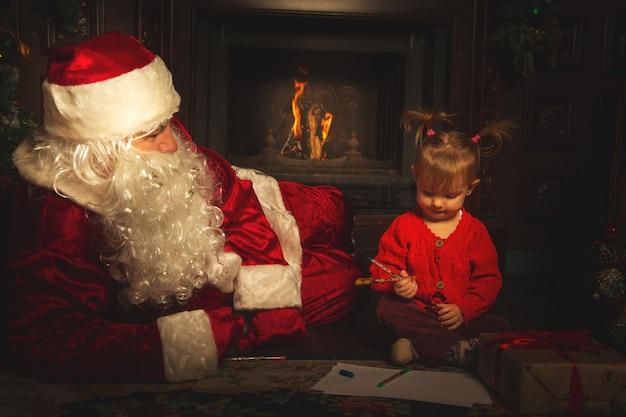 Echte weihnachtsmann spielt mit kindern in der nähe des weihnachtsbaumes.