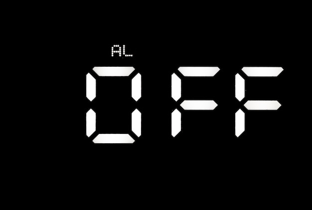 Echte weiße led-digitaluhr auf schwarzem hintergrund mit alarm aus