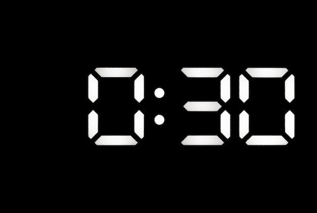 Echte weiße led-digitaluhr auf schwarzem hintergrund mit zeit 030