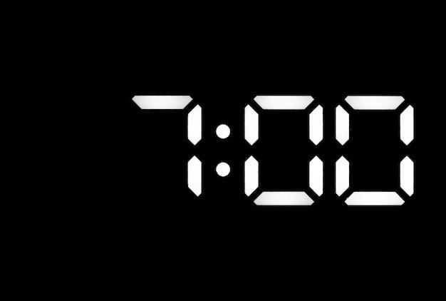 Echte weiße led-digitaluhr auf schwarzem hintergrund mit zeit 700