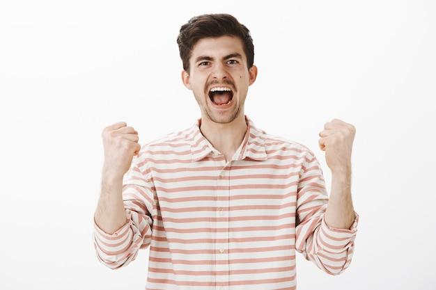 Echter fan, der sich über sein lieblingsteam freut. wir sehen einen triumphierenden gutaussehenden männlichen mitarbeiter, der vor glück und sieg schreit, geballte fäuste hebt, den sieg feiert und sich wie ein champion über der grauen wand fühlt