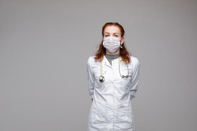 Echter held in weißem mantel, gesichtsmaske und stethoskop.