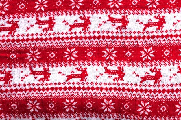 Echter roter gestrickter hintergrund mit weißen weihnachtshirschen und schneeflocken.