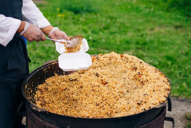 Echter usbekischer pilaw in einem riesigen kessel. nationalgerichte kochen.