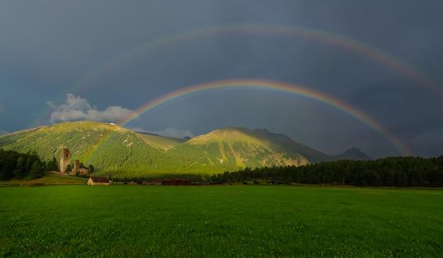 Echter voller doppelter regenbogen auf einer bergwiese
