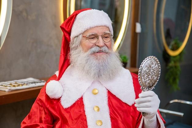 Echter weihnachtsmann im friseursalon mit einem spiegel, der sich selbst anschaut.