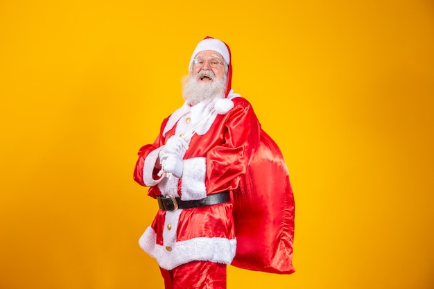 Echter weihnachtsmann mit rotem hintergrund, mit brille, handschuhen und einer hutseite.